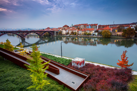 Maribor, Slovenia. Cityscape image of Maribor, Slovenia during autumn twilight with reflection of the city in Drava River.