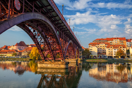 Maribor, Slovenia. Cityscape image of Maribor, Slovenia during autumn day with reflection of the city in Drava River.