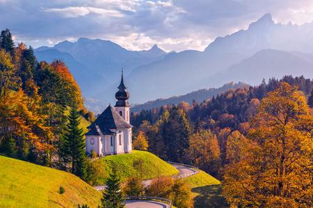 Autumn in Alps. Image of the Bavarian Alps with Maria Gern Church and Watzmann mountain during beautiful autumn sunset. Stock Photo