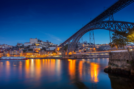 Porto, Portugal. Cityscape image of Porto, Portugal with reflection of the city in the Douro River and the Luis I Bridge during twilight blue hour.