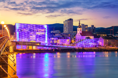 Linz, Austria. Cityscape image of riverside Linz, Austria during twilight blue hour with reflection of the city lights in Danube river.