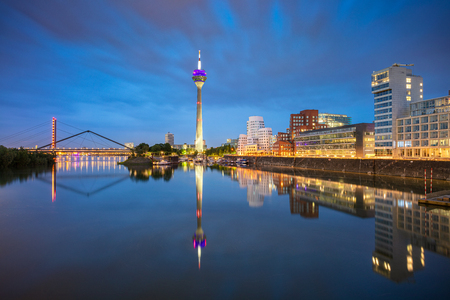 Cityscape image of Düsseldorf, Germany with the Media Harbour and reflection of the city in the Rhine river, during twilight blue hour., Dusseldorf, Germany. Stock Photo