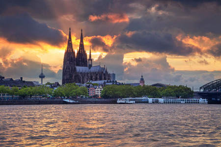 Cityscape image of Cologne, Germany with Cologne Cathedral and Hohenzollern Bridge during dramatic sunset, Cologne, Germany.