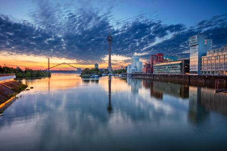 Düsseldorf, Germany. Cityscape image of Düsseldorf, Germany with the Media Harbour and reflection of the city in the Rhine river, during sunrise.