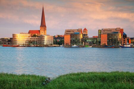 Rostock, Germany. Cityscape image of Rostock riverside with St. Peters Church during summer sunset.