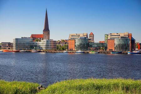 Rostock, Germany. Cityscape image of Rostock riverside with St. Peters Church during sunny summer day. Stock Photo