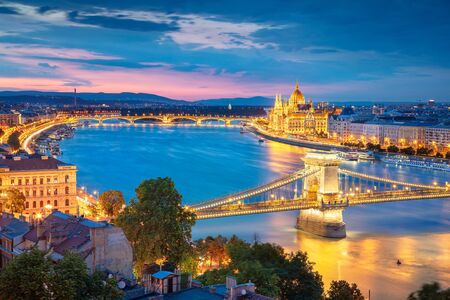 Aerial cityscape image of Budapest with Chain Bridge and parliament building during summer sunset.