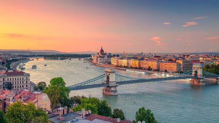 Panoramic aerial cityscape image of Budapest panorama with Szechenyi Chain Bridge and parliament building during summer sunset. Stock Photo - 127906292