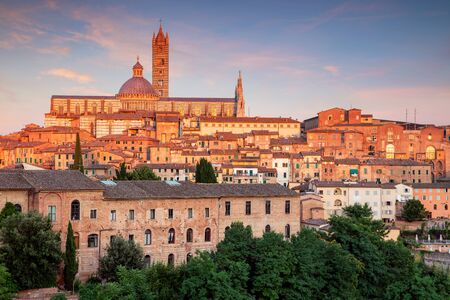 Siena. Aerial cityscape image of medieval city of Siena, Italy during sunset.