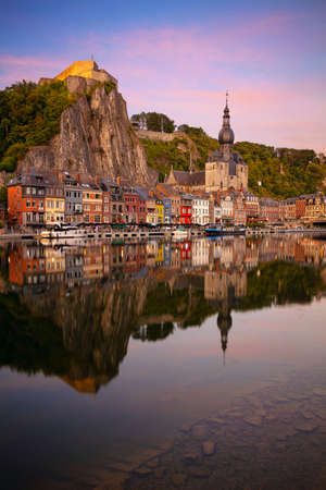 Dinant, Belgium. Cityscape image of beautiful historical city of Dinant with the reflection of the city in the Meuse River at summer sunset.