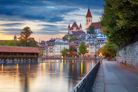 Thun, Switzerland. Cityscape image of beautiful city of Thun with the reflection of the city in the Aare river at sunset.
