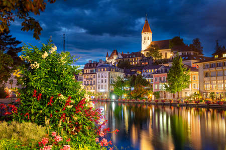 Thun, Switzerland. Cityscape image of beautiful city of Thun with the reflection of the city in the Aare river at night.