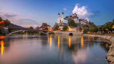Aarburg, Switzerland. Panoramic cityscape image of beautiful city of Aarburg with the reflection of the city in the Aare river at sunset. Stock Photo