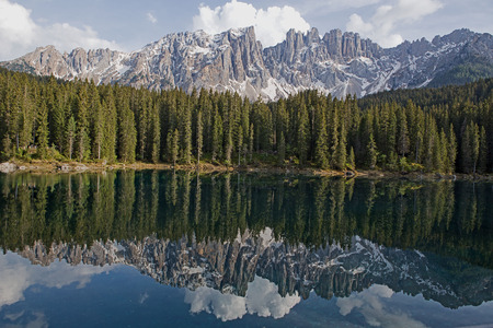 The peaks of the Latemar group in the South Tyrolean Dolomites are reflected in Lake Karer