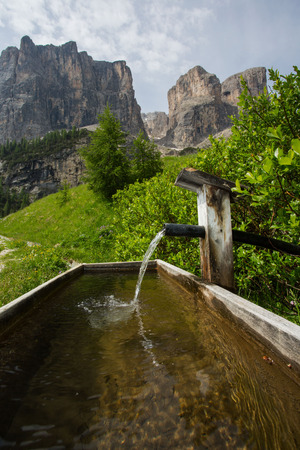 Spring water in front of the panorama of the Dolomites with Sellastock on the Groednerpass road
