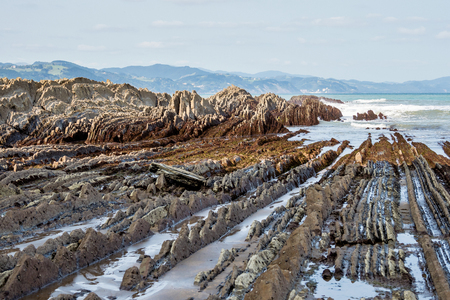 The Itzurum Flysch in Zumaia - Basque Country. Flysch is a sequence of sedimentary rock layers that progress from deep-water and turbidity flow deposits to shallow-water shales and sandstones. Stock fotó
