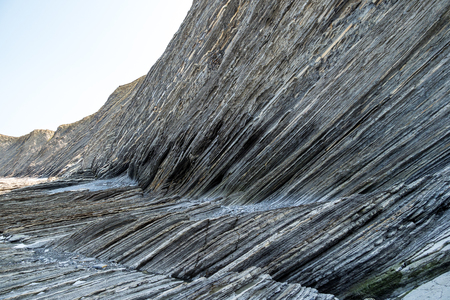 Flysch Coast of Sakoneta, Zumaia, Spain. Flysch is a sequence of sedimentary rock layers that progress from deep-water and turbidity flow deposits to shallow-water shales and sandstones.