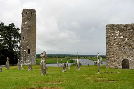 Ruins of medieval stone Christian church called Temple Melaghlin in Clonmacnoise in Ireland. The ancient monastic city of Clonmacnoise with the typical crosses and graves Imagens