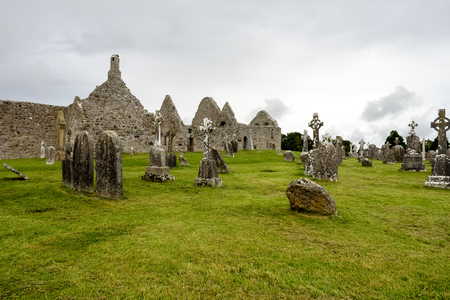 Ruins of medieval stone Christian church called Temple Melaghlin in Clonmacnoise in Ireland. The ancient monastic city of Clonmacnoise with the typical crosses and graves Archivio Fotografico - 118554616