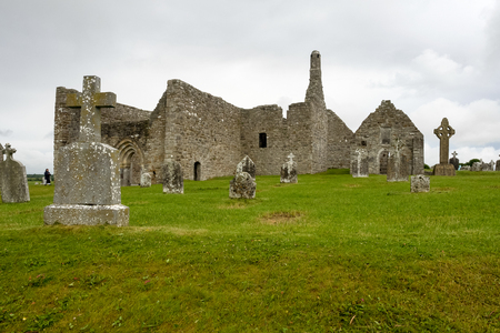 Ruins of medieval stone Christian church called Temple Melaghlin in Clonmacnoise in Ireland. The ancient monastic city of Clonmacnoise with the typical crosses and graves Archivio Fotografico - 118554628