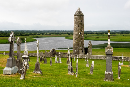 Ruins of medieval stone Christian church called Temple Melaghlin in Clonmacnoise in Ireland. The ancient monastic city of Clonmacnoise with the typical crosses and graves Archivio Fotografico - 118554643