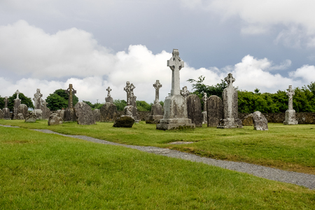 Ruins of medieval stone Christian church called Temple Melaghlin in Clonmacnoise in Ireland. The ancient monastic city of Clonmacnoise with the typical crosses and graves Archivio Fotografico - 118561812
