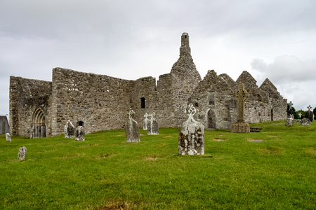 Ruins of medieval stone Christian church called Temple Melaghlin in Clonmacnoise in Ireland. The ancient monastic city of Clonmacnoise with the typical crosses and graves Archivio Fotografico - 121047642