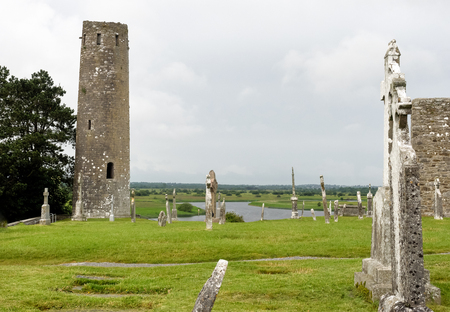 Ruins of medieval stone Christian church called Temple Melaghlin in Clonmacnoise in Ireland. The ancient monastic city of Clonmacnoise with the typical crosses and graves Archivio Fotografico - 125779798