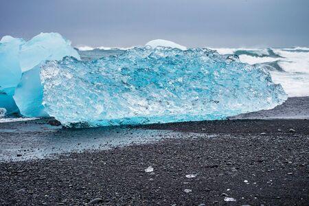 Iceberg at Diamond Beach Joekulsarlon. Blue chunk of ice on the black sand beach near the Glacier Lagoon in Iceland