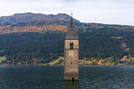 Der berühmte Glockenturm im Reschensee - Lago di Resia in Südtirol, Italien. Während des 2. Weltkrieges wurde ein Damm gebaut und das Dorf unter Wasser gesetzt, nur der Turm ist heute noch sichtbar. Standard-Bild