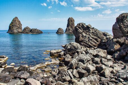 A Cyclops island, basaltic rock fomation, viwed from the port of Aci Trezza, Catania, Sicily, Italy.