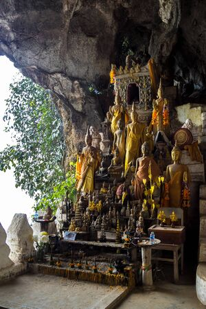 Hundreds of old and faded Buddha statues inside the Tham Ting Cave at the famous Pak Ou Caves near Luang Prabang in Laos. Banco de Imagens