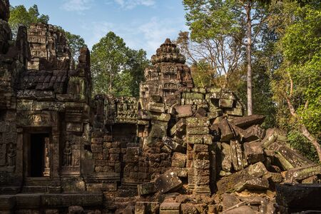 Ancient ruins of Ta Som temple in Angkor Wat complex, Cambodia. Stone temple ruin with jungle tree aerial roots. Abandoned temple demolished by tropical jungle. Banco de Imagens