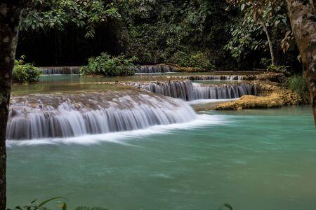 Tat Kuang Si Falls near Luang Prabang, Laos - Exotic travertine turquoise blue cascading waterfalls in Asia.