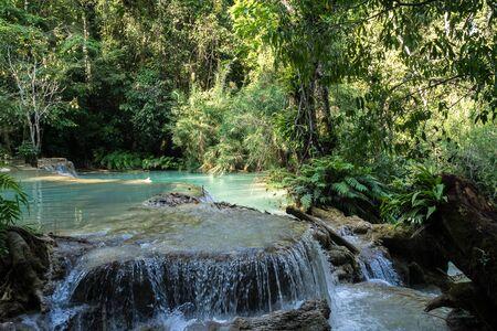 Tat Kuang Si Falls near Luang Prabang, Laos - Exotic travertine turquoise blue cascading waterfalls in Asia. Banco de Imagens - 128590554