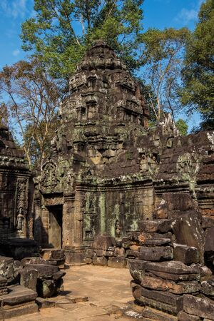 Ancient ruins of Ta Som temple in Angkor Wat complex, Cambodia. Stone temple ruin with jungle tree aerial roots. Abandoned temple demolished by tropical jungle. Фото со стока