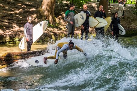 Munich, Germany - July 13, 2019: Surfer in the city river, Munich is famous for people surfing in urban enviroment called Eisbach Sajtókép