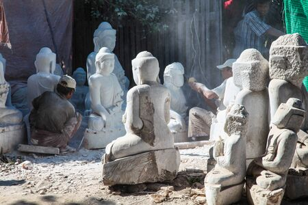 carving Buddha statues from stone in a street workshop in Mandalay, Myanmar Stockfoto