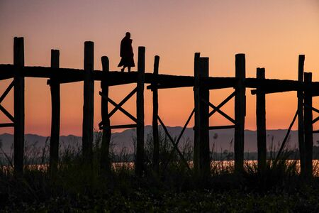 Silhouette of U Bein Bridge at sunrise. It is a crossing that spans Taungthaman Lake, Amarapura in Myanmar, former Burma. Oldest and longest teakwood bridge of the world. Stockfoto