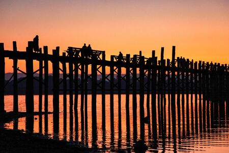 Silhouette of U Bein Bridge at sunrise. It is a crossing that spans Taungthaman Lake, Amarapura in Myanmar, former Burma. Oldest and longest teakwood bridge of the world. Stok Fotoğraf