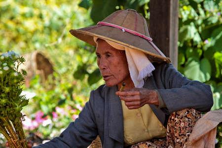 Heho, Myanmar - Nov 08, 2019: Smoking woman at a market in the city center of Heho in Myanmar, former Burma in Asia Redactioneel