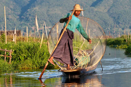 Inle Lake, Myanmar - Nov 08, 2019: Fisherman rowing boat by one leg on Inle Lake, Myanmar. Inle Lake is famous for its floating villages and gardens.
