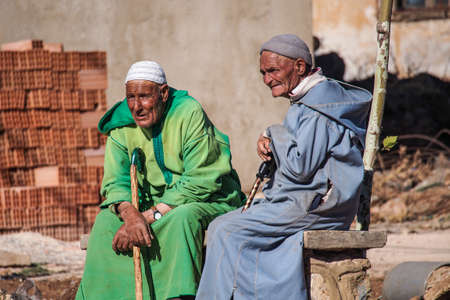 Fes, Morocco - Oct 16, 2019: Two old men sitting at Bab Boujloud, or the Blue Gate to old Medina Fez El Bali.