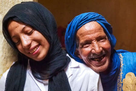 Erfoud, Morocco - Oct 17, 2019: Old Berber man with his daughter living in the moroccan mountains in Ksar Maadid near Erfoud in Morocco, Africa
