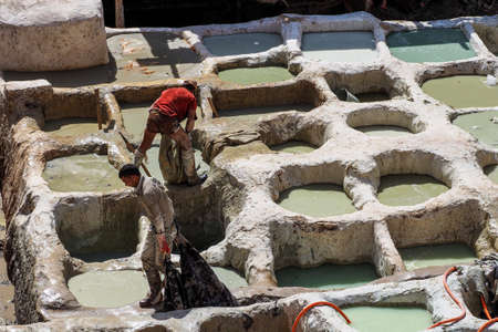 Fes, Morocco - Oct 15, 2019: Tanneries of Fes, Morocco, Africa. Old tanks of the tanneries in Fes with color paint for leather