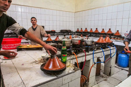 Ouarzazate, Morocco - Oct 21, 2019: Young moroccan man cooking tajine with vegetables and showing it to the tourist to sell meal in Ouarzazate, Morocco. Redactioneel