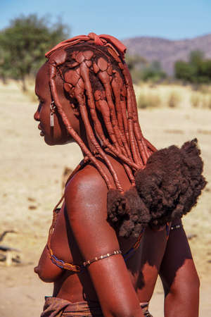 Opuwo, Namibia - Jul 07, 2019: Unidentified Himba woman with the typical necklace and hairstyle in himba tribe village