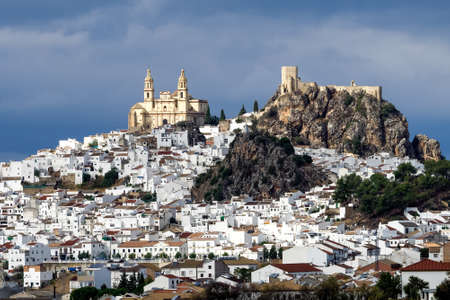 View of Olvera village, one of the beautiful white villages, Pueblos Blancos of Andalucia, Spain. It features a moorish fortress and a neoclassic cathedral overlooking the whitewashed village.