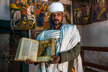 Yeha, Ethiopia - Feb 10, 2020: an orthodox priest shows a painted holy bible from the 14th century in the Great Temple of the Moon, privy to walia ibex in Yeha, Ethiopia 新聞圖片