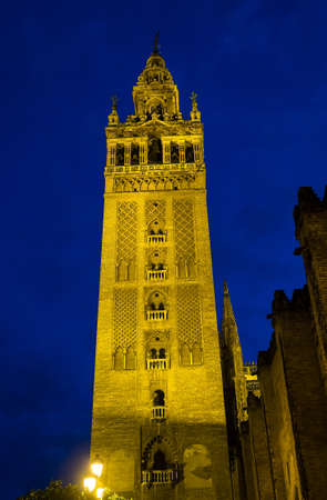 Famous Bell Tower named Giralda in catholic Cathedral of Saint Mary, Catedral de Santa Maria de la Sede in Seville, Andalusia, Spain at night 免版税图像